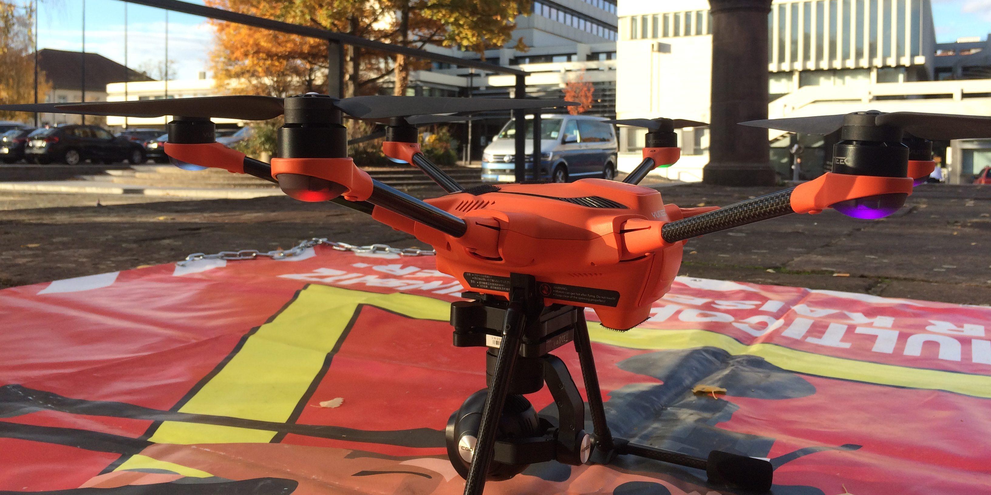 Eine orangefarbene Drohne steht auf dem Boden