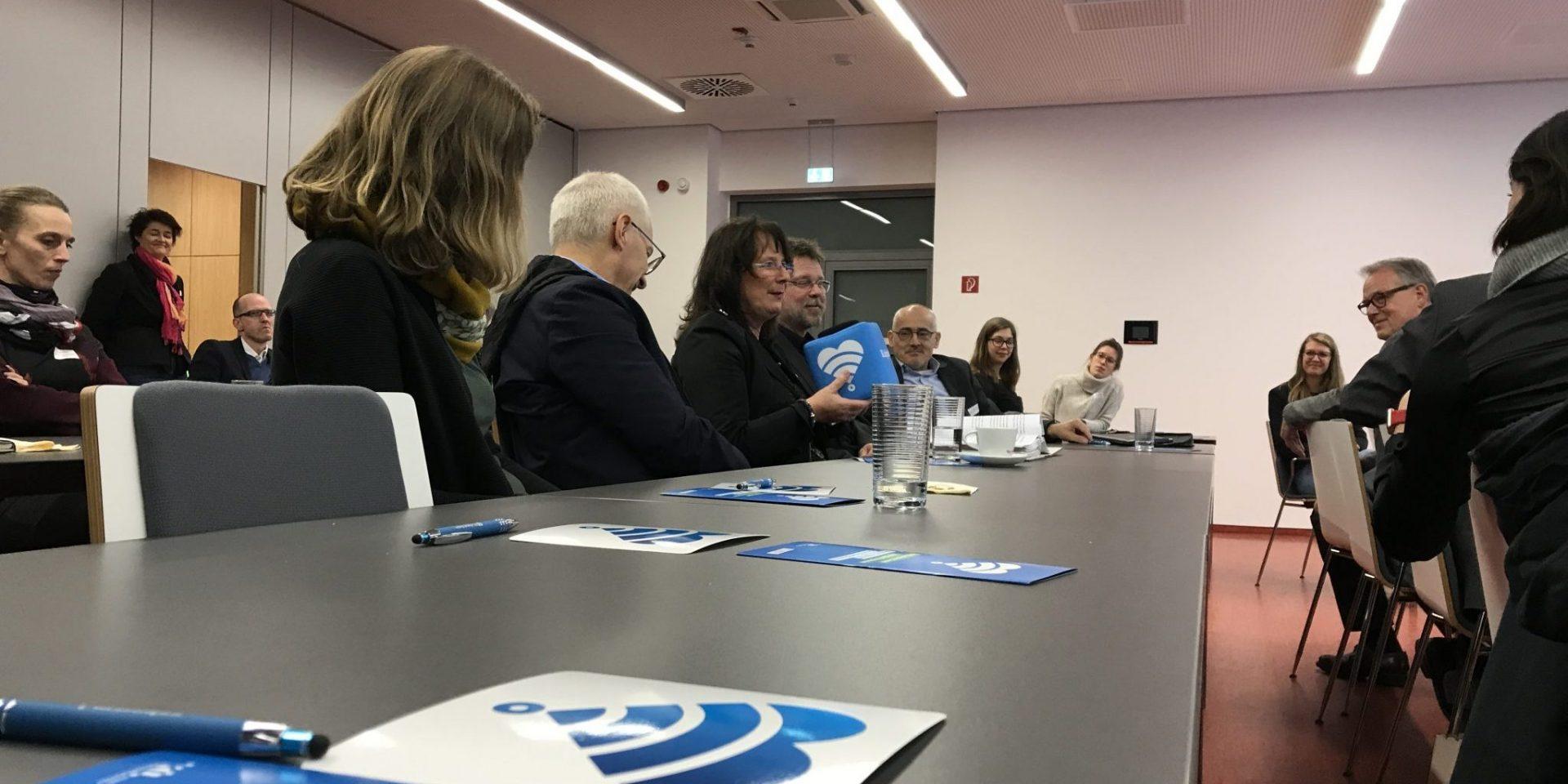 Mehrere Menschen sitzen in Tischreihen hintereinander. Eine Frau spricht in ein Mikrofon.