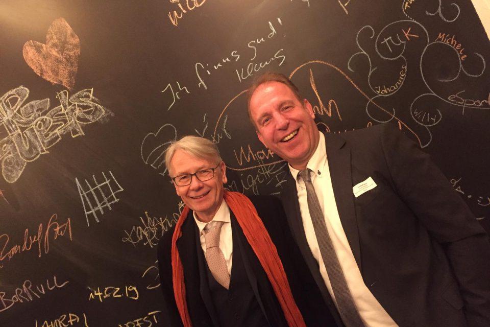 Zwei Männer (Oberbürgermeister Dr. Klaus Weichel und Staatssekretär Randolf Stich) stehen vor einer Kreidetafel nebeneinander.