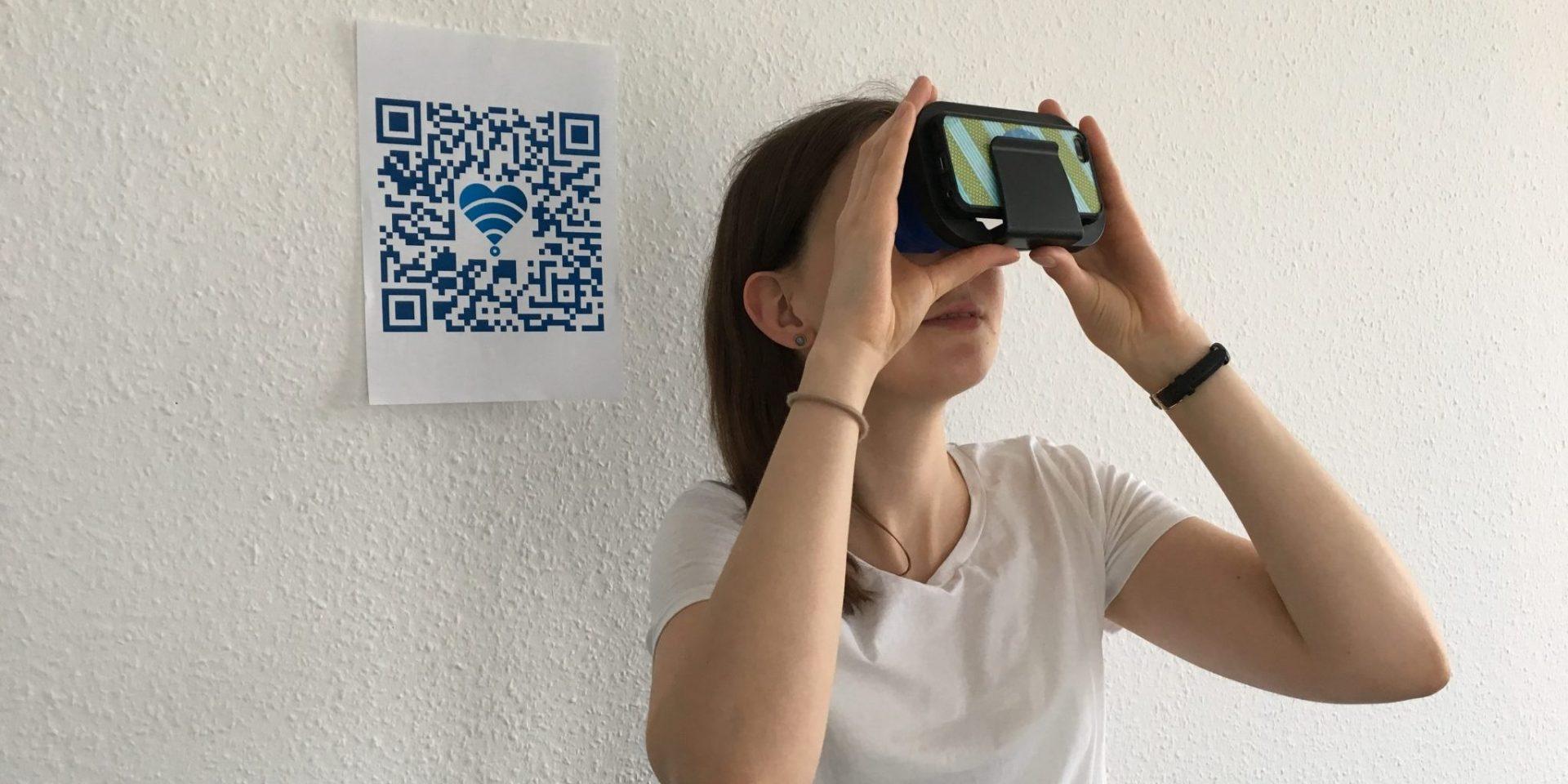 Eine Frau schaut mithilfe eines Cardboards etwas an. Neben ihr an der Wand ist ein QR-Code angebracht.