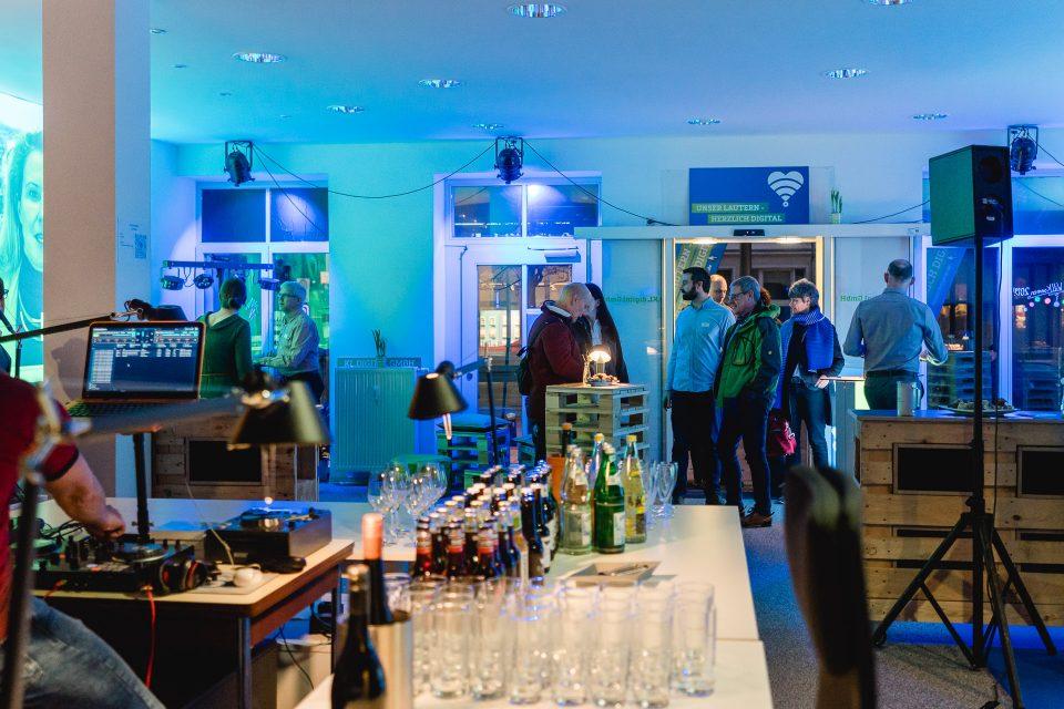 Mehrere Menschen stehen bei einer Veranstaltung in einem Raum. Im Vordergrund stehen Getränke, neben einem DJ-Pult.