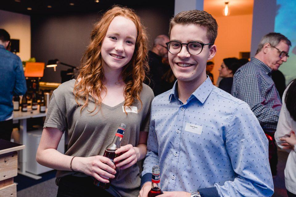 Eine junge Frau und ein junger Mann lächeln in die Kamera