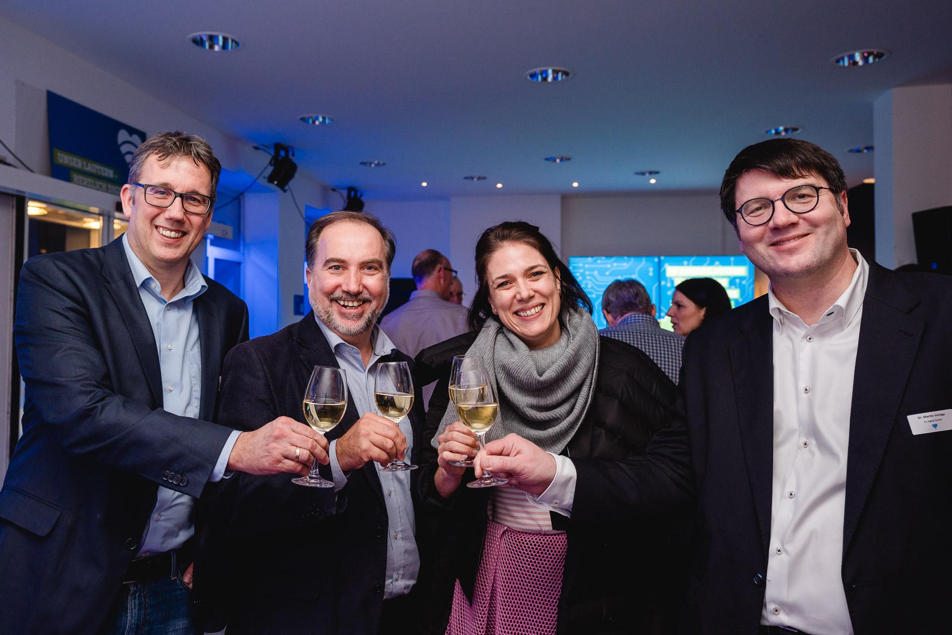 Vier Personen (drei Männer, eine Frau) schauen in die Kamera und prosten sich mit Weißwein zu.