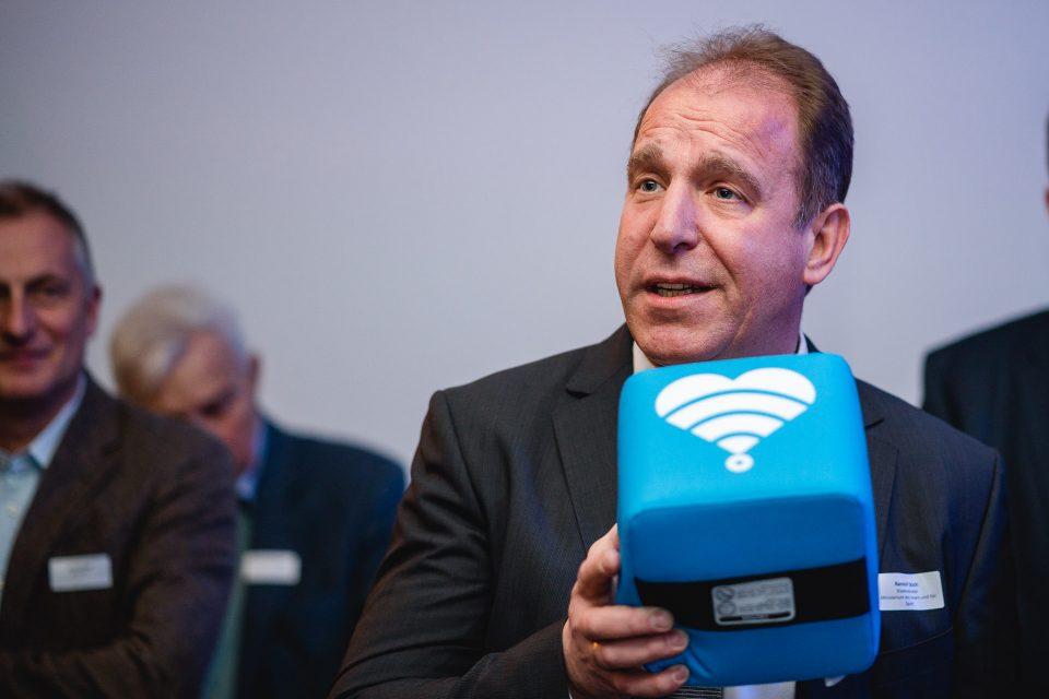 Ein Mann (Staatssekretär Randolf Stich) hat ein blaues Mikrofon in der Hand und spricht.