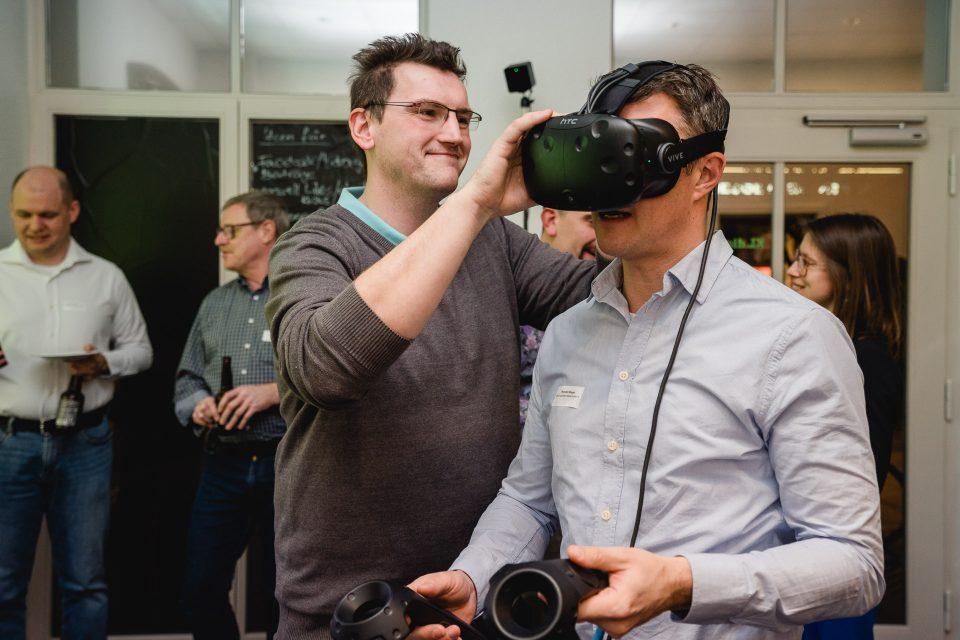 Ein Mann richtet einem anderen Mann die VR-Brille, die dieser trägt.