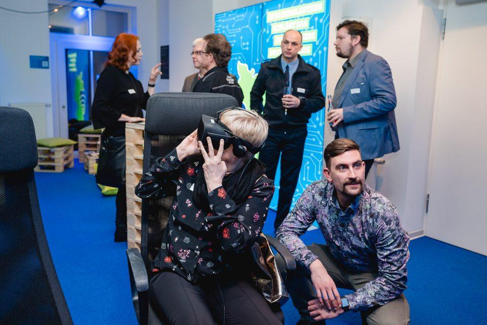 Eine Frau, die eine VR-Brille trägt, schaut zur Seite. Neben ihr hockt ein Mann und schaut in eine andere Richtung (auf einen Monitor außerhalb des Bildes).