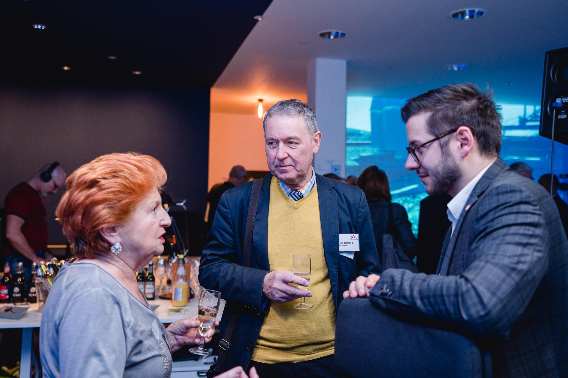 Drei Personen (eine Frau und zwei Männer) stehen auf einer Feier beieinander und unterhalten sich.