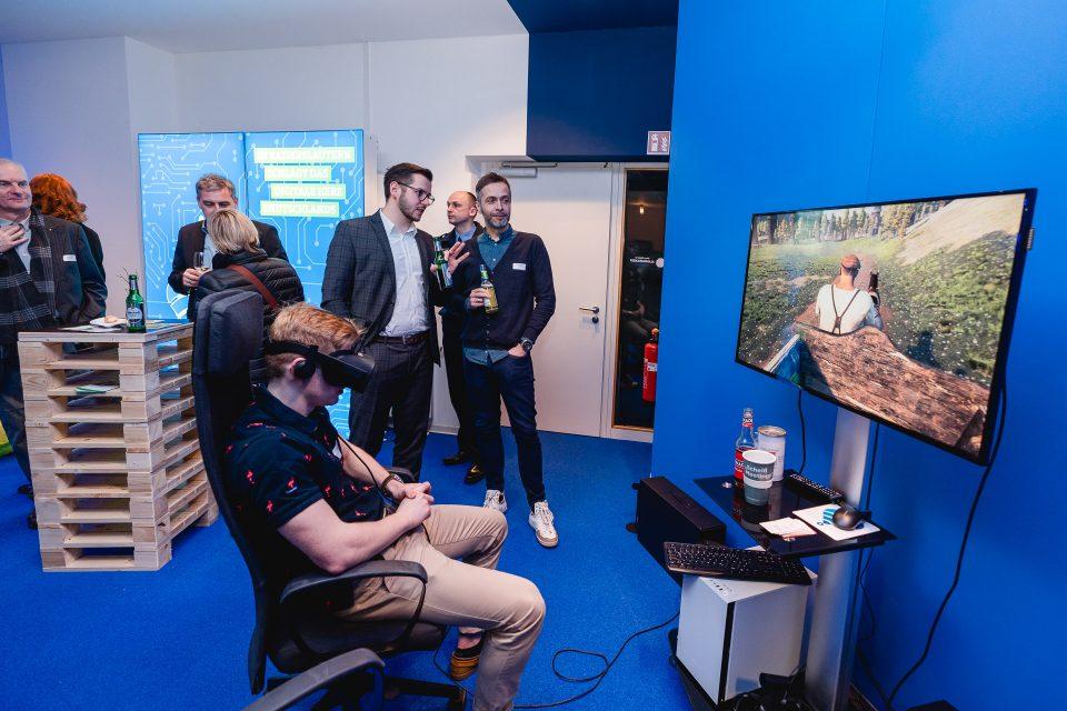 Ein junger Mann sitzt mit einer VR-Brille auf dem Kopf auf einem Stuhl. Auf einem Monitor sieht man die Rückenansicht eines Kutschers.
