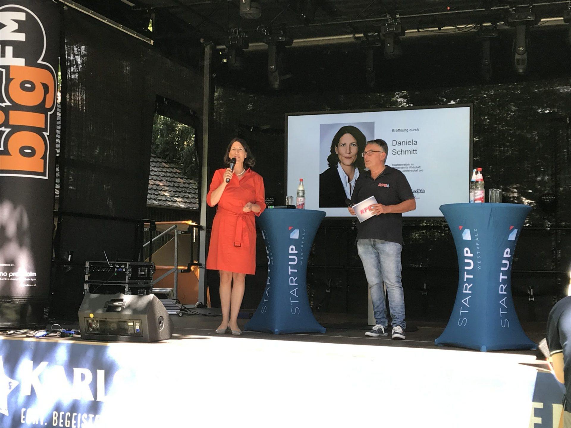 Staatssekretärin Daniela Schmitt eröffnet das Startup Festival. Dafür steht sie neben einem Moderator auf einer Bühne.