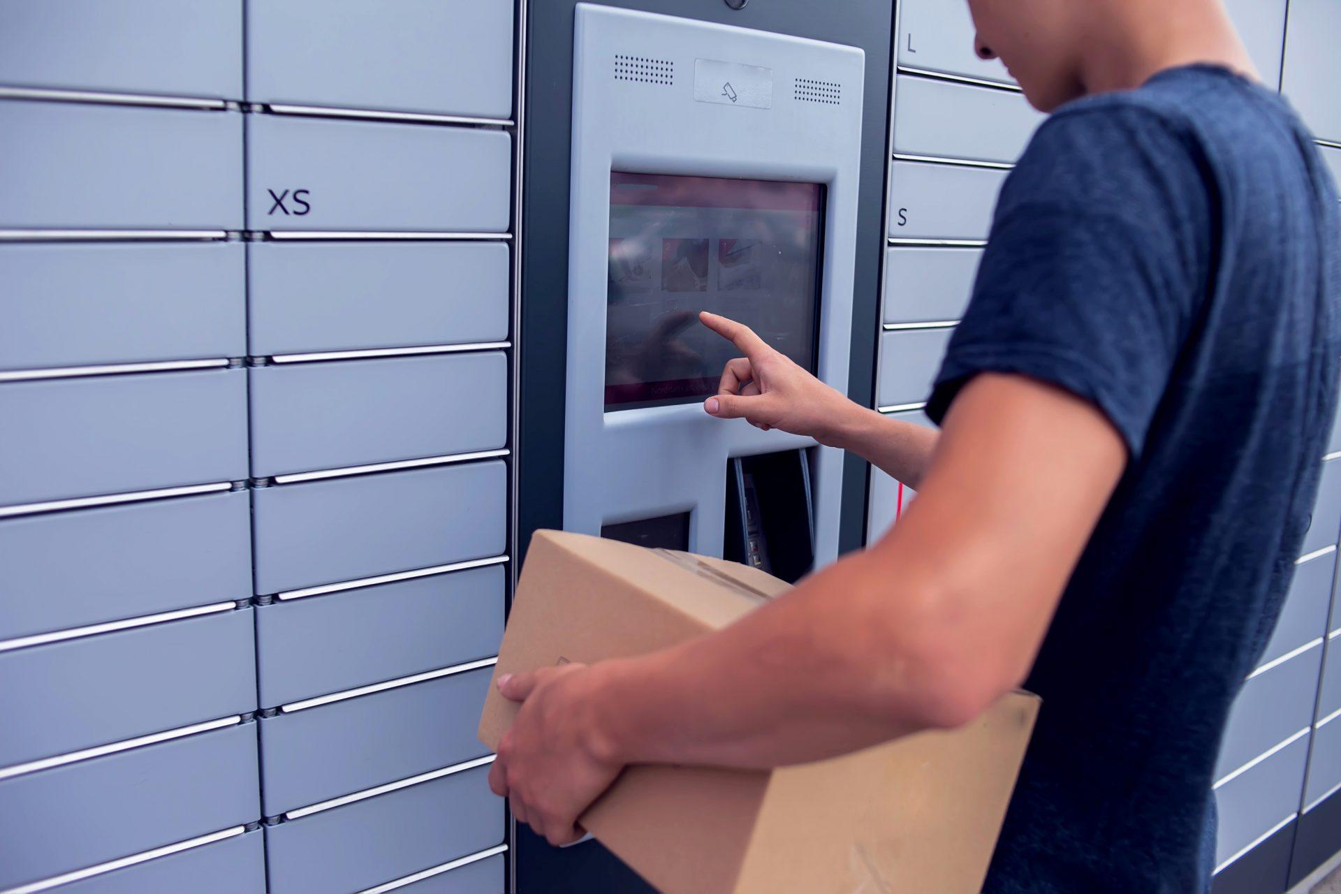 Ein Mann steht mit einem Paket unter dem Arm vor einer Packstation