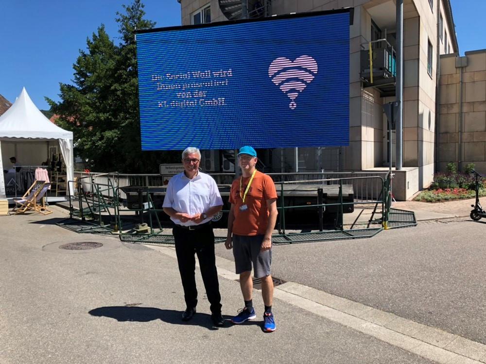 Mitarbeiter Martin Wilke steht zusammen mit Innenminister Roger Lewentz vor einer Präsentationsleinwand auf dem Festgelände in Annweiler. Auf der Leinwand steht