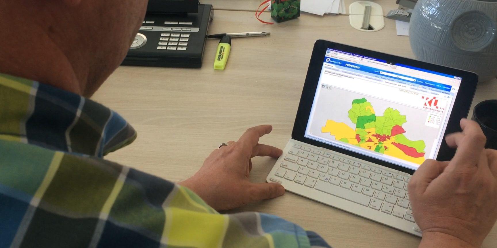 Ein Mann betrachtet auf einem Tablet eine Stadtkarte Kaiserslauterns mit Statistiken