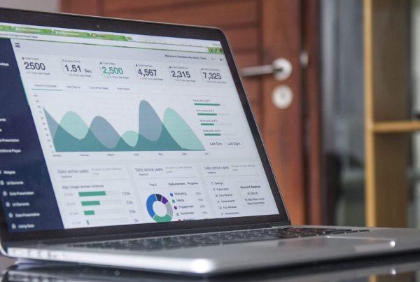 Ein geöffnetes Laptop steht auf einem Tisch. Auf dem Bildschirm sind verschiedene Statistiken zu sehen.