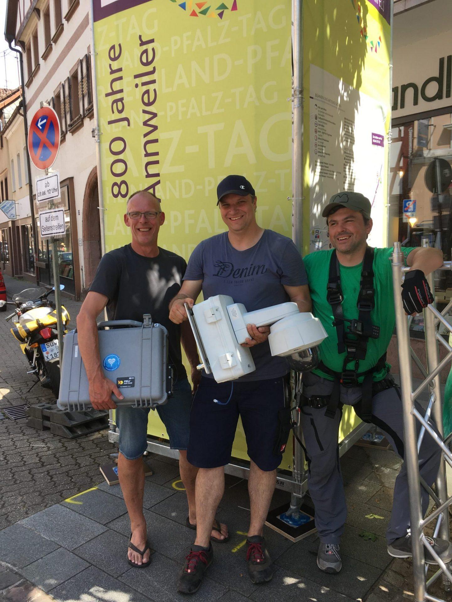 Drei Männer von KL.digital bzw. der Polizei stehen vor einem Bannerturm. In der Hand haben sie Equipment, z.B. Koffer und eine Überwachungskamera