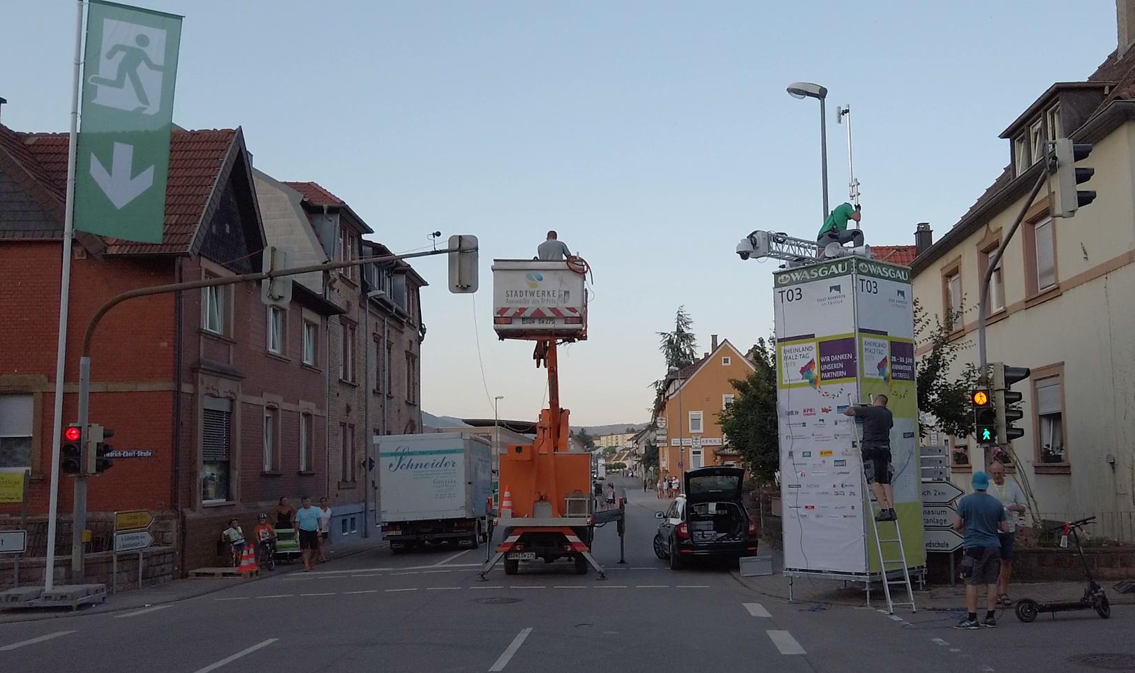 Eine Hebebühne steht in Annweiler auf einer Straße, Männer verlegen Kabel und bauen Masten auf.
