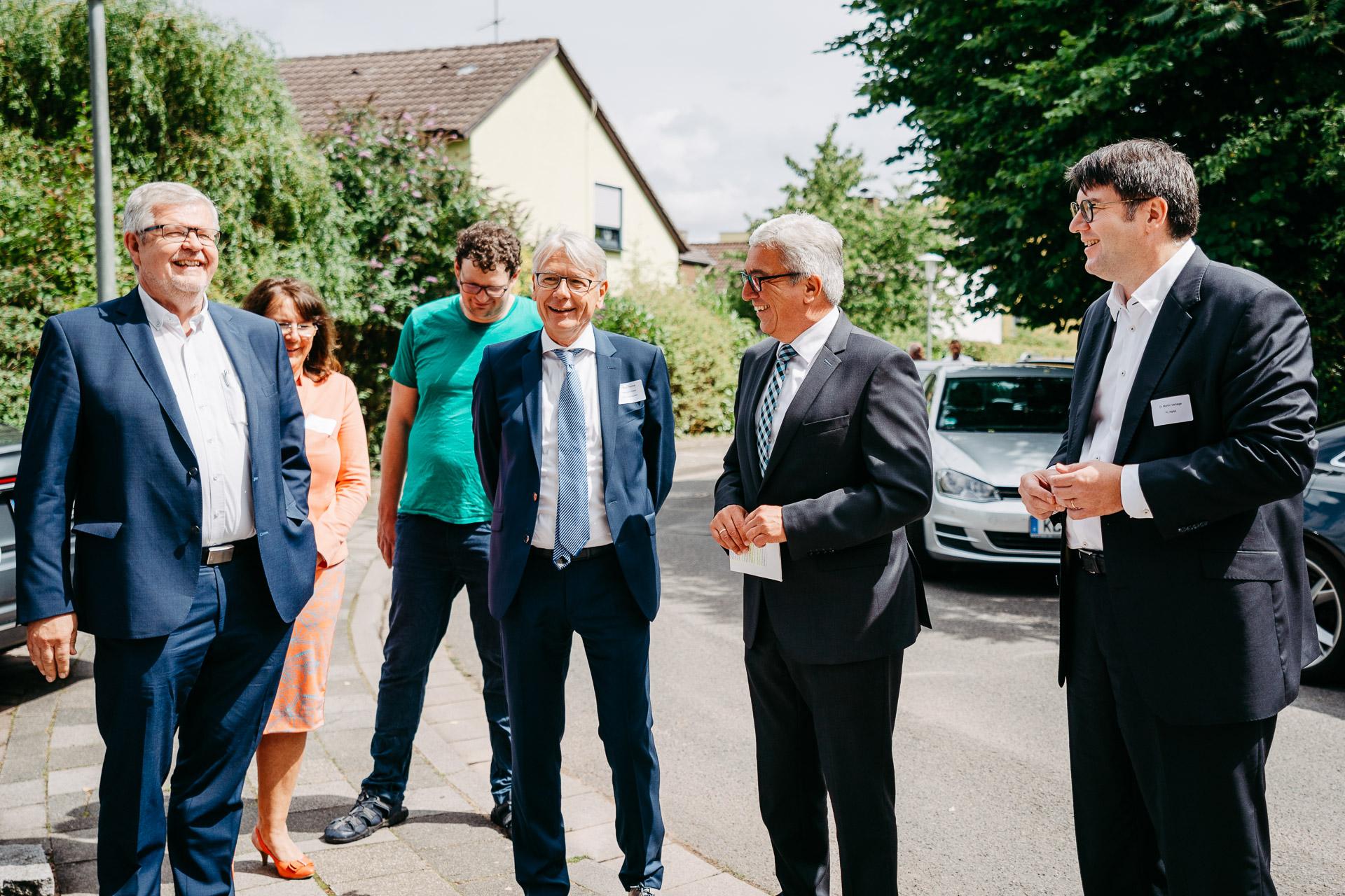 Vier Männer stehen im Bildvordergrund auf einem Gehweg und sind fröhlich.