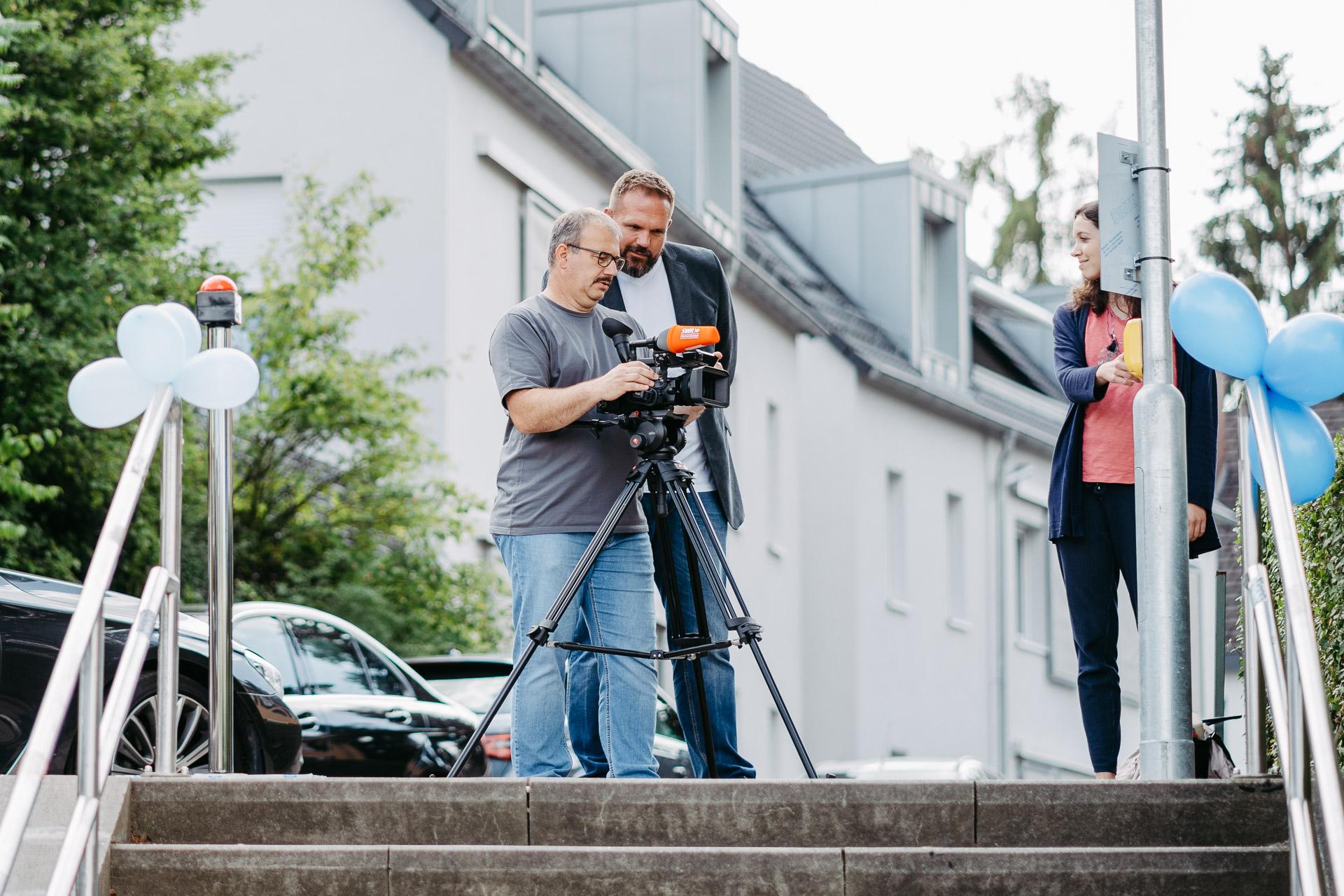 Zwei Männer stehen an einer Kamera und filmen eine Reporterin, die einen Knopf an einer Straßenlaterne im Fauthweg betätigt.