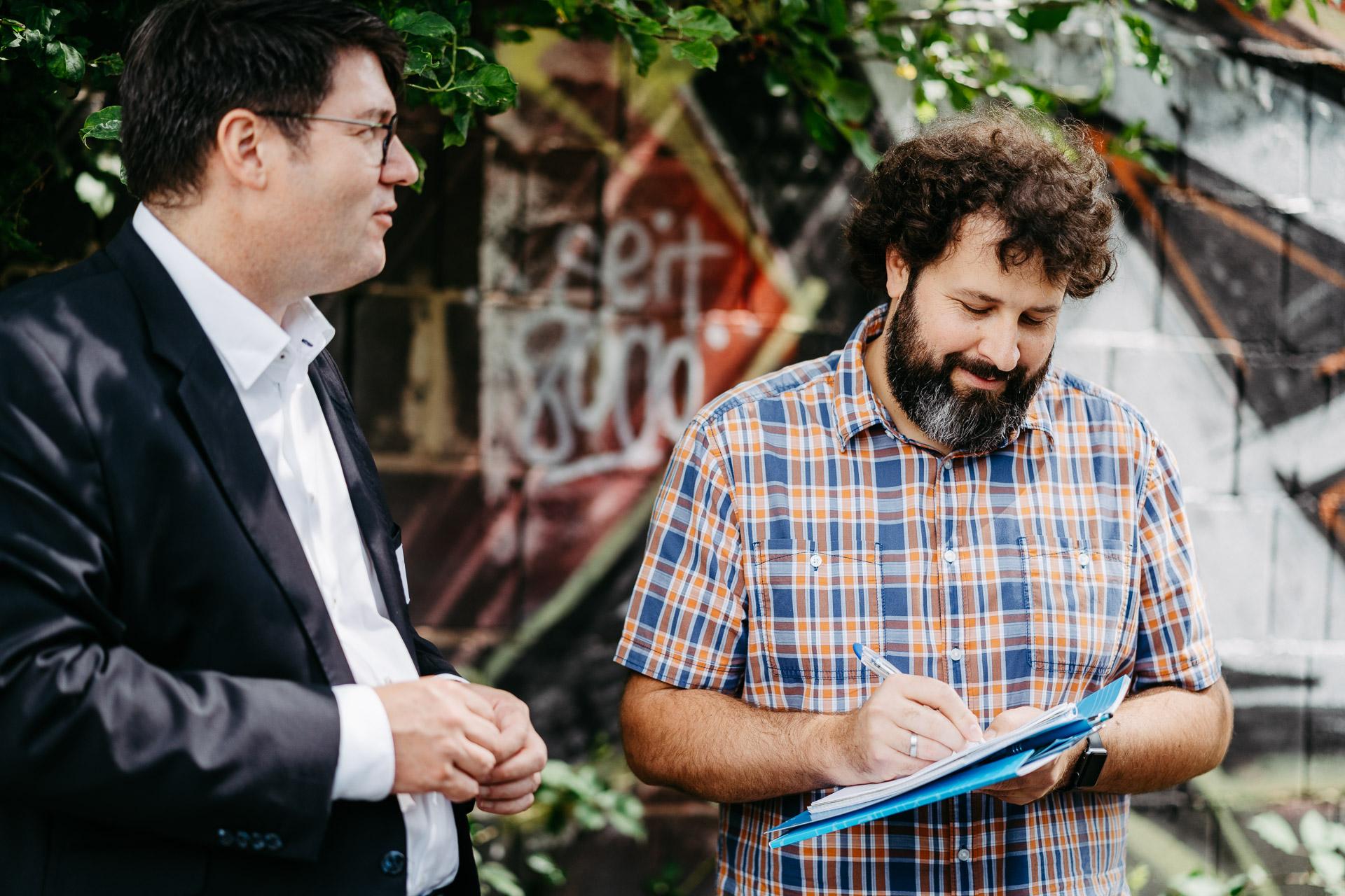 Zwei Männer sind im Gespräch, einer macht sich Notizen.
