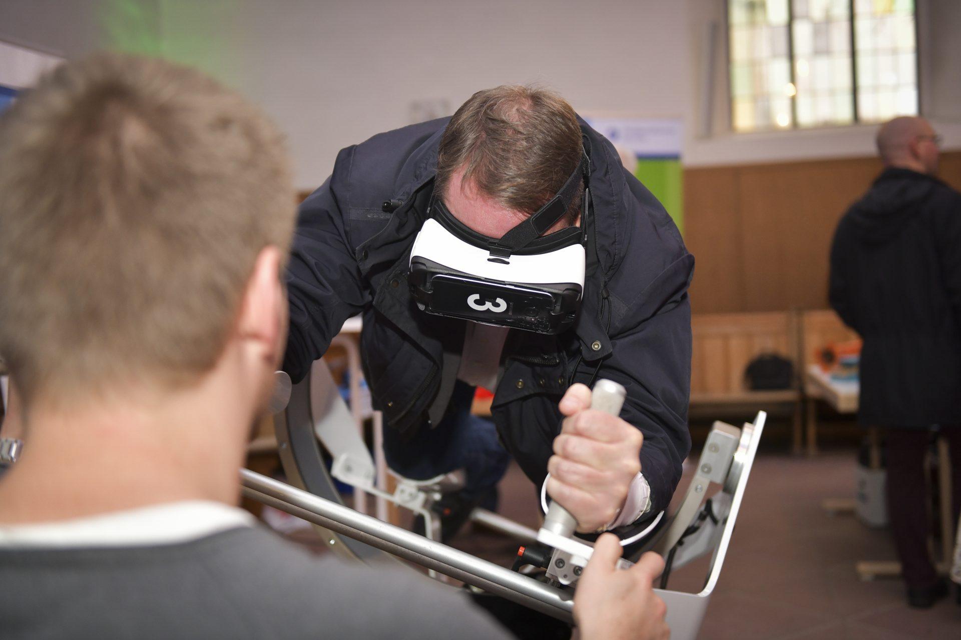 Ein Mann liegt in einem Virtual-reality-Flugsimulator.