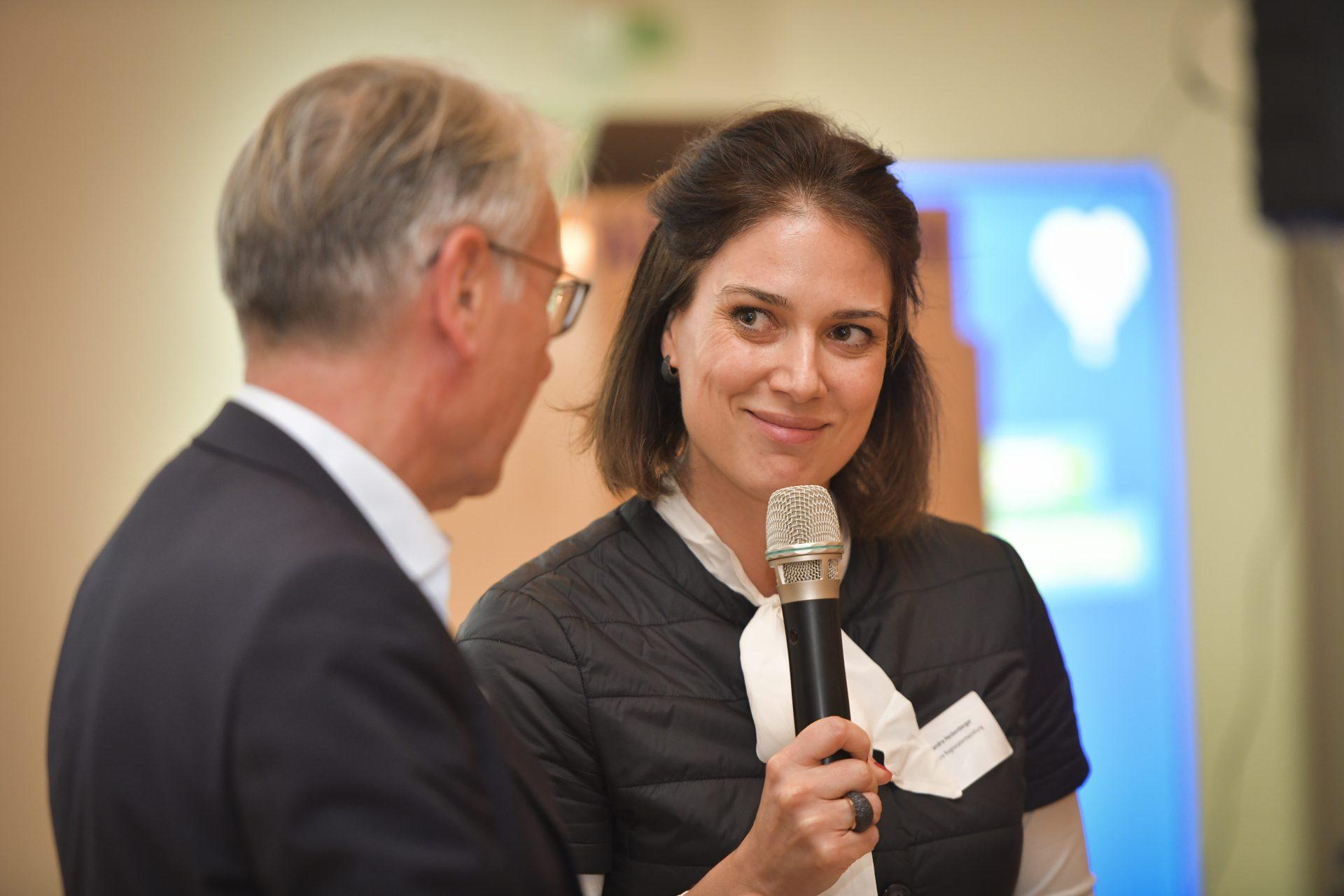 Eine Frau führt vor Publikum ein Interview mit einem Mann.