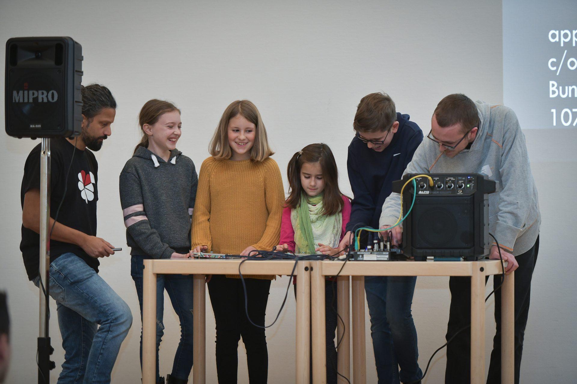 Zwei Betreuer stehen mit Kindern auf einer Bühne und machen elektronische Musik.