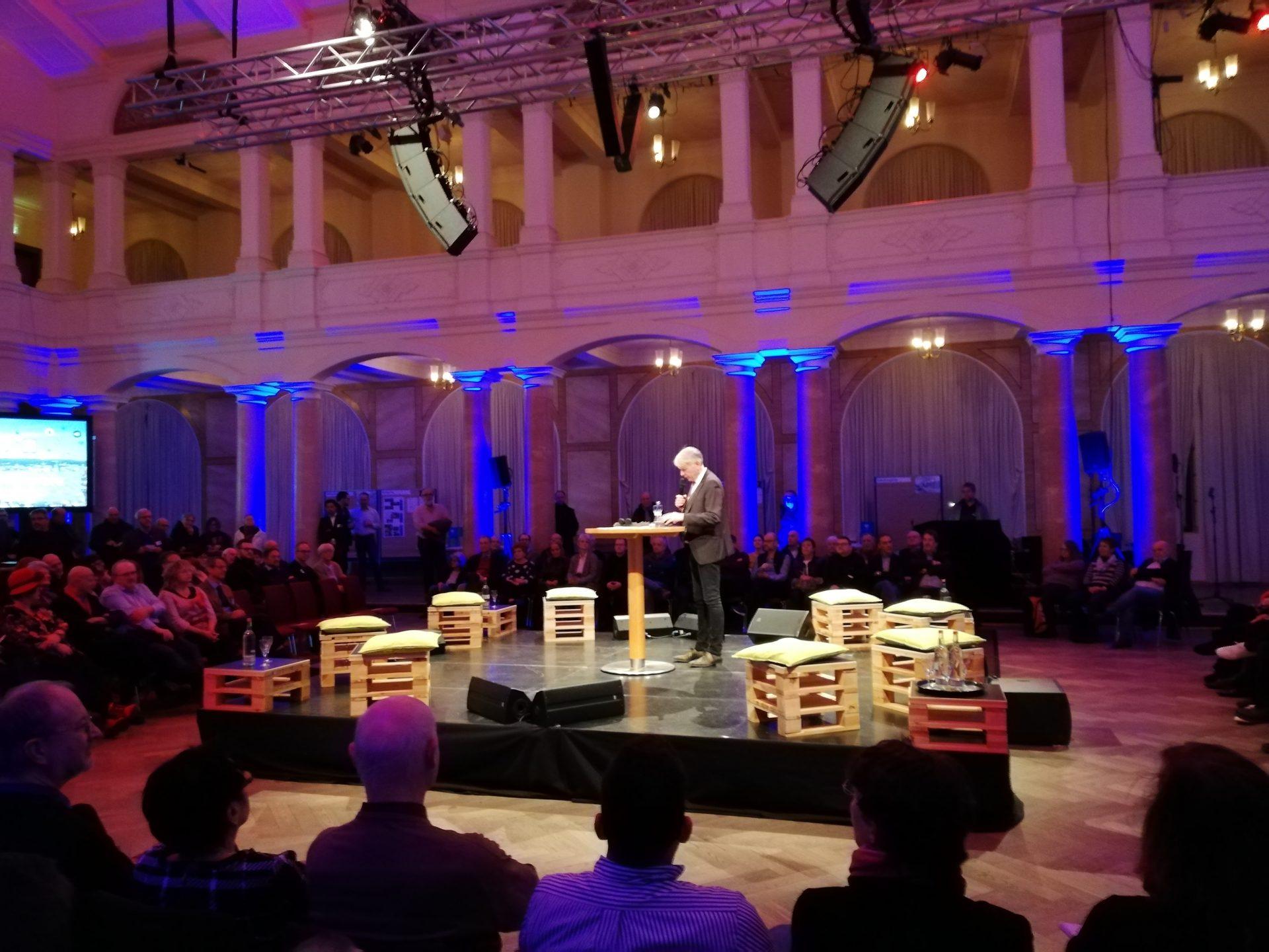 Der Oberbürgermeister steht bei der Eröffnung der Veranstaltung auf einer Bühne inmitten des Publikums.