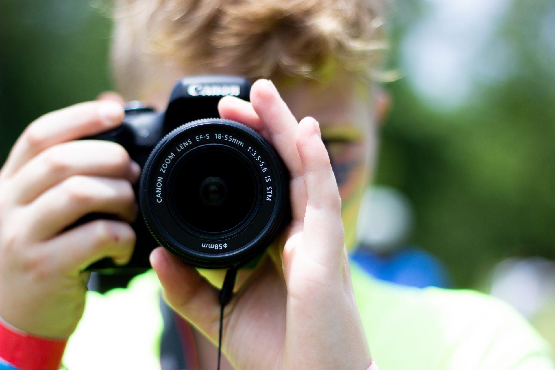 Eine Person richtet eine Kamera auf den Betrachter