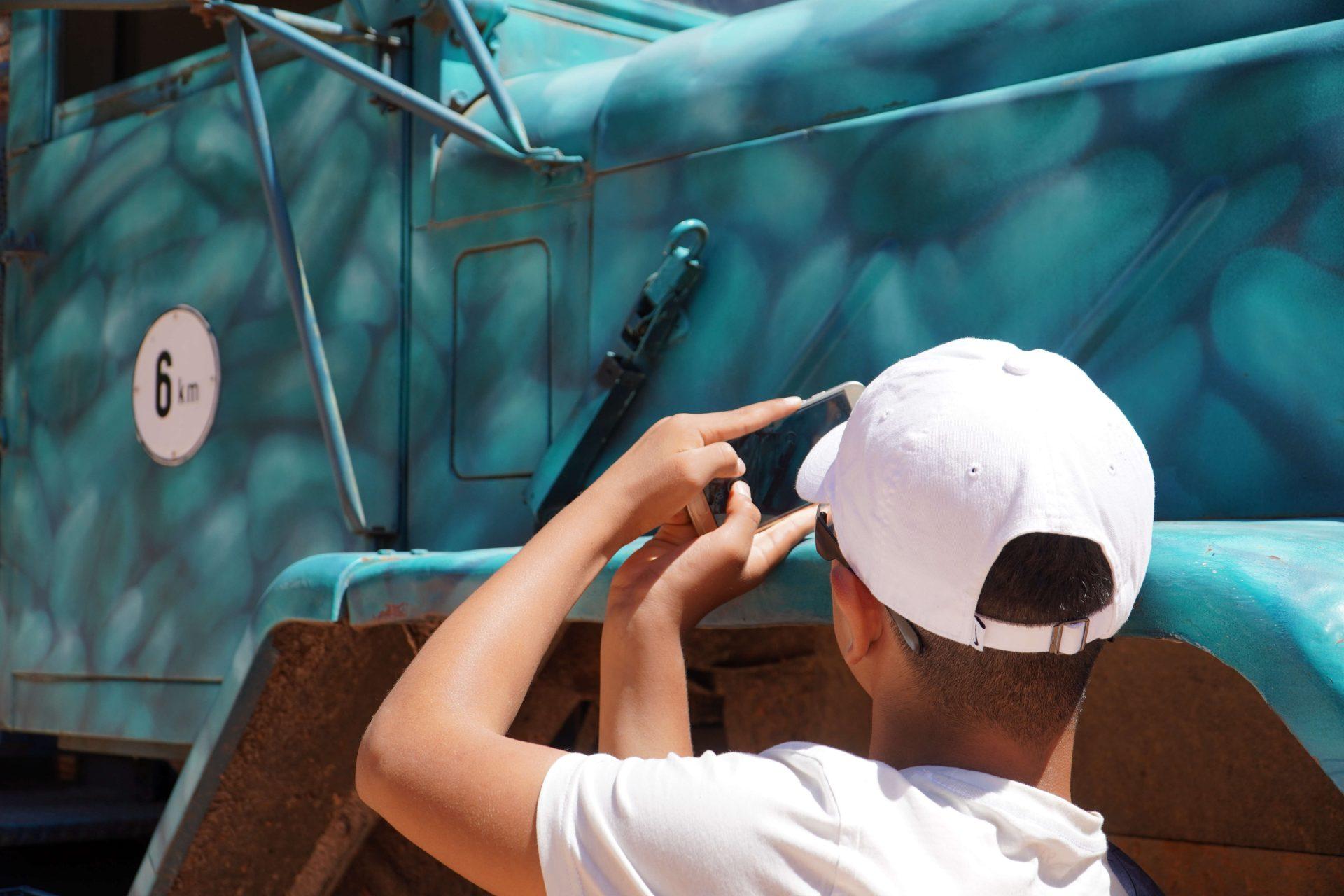 Ein Junge fotografiert einen LKW mit seinem Handy.