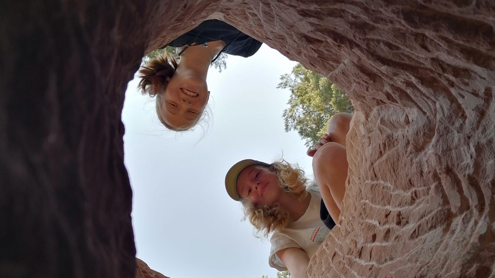 Zwei Mädchen schauen durch ein Steinloch nach unten