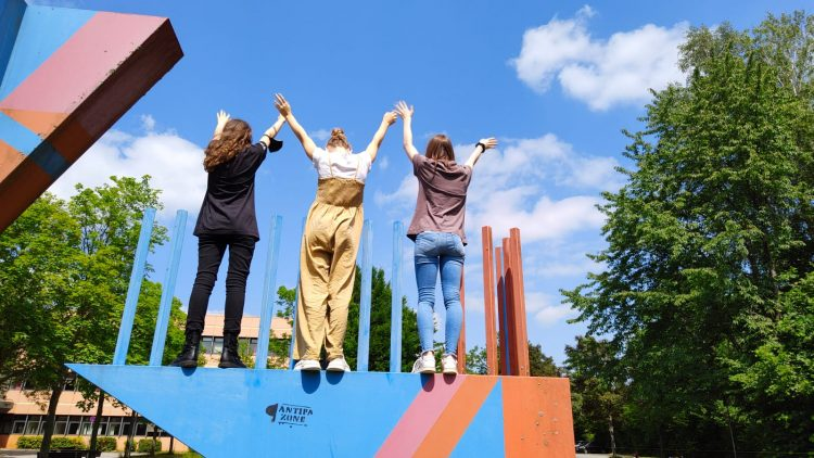 Drei Mädchen stehen auf einem Kunstwerk