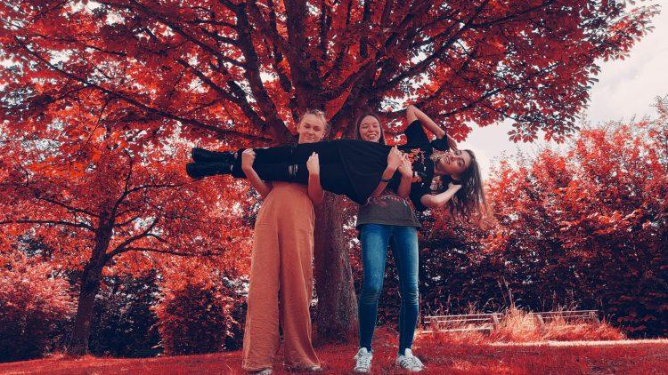 Zwei Mädchen halten ein weiteres Mädchen quer
