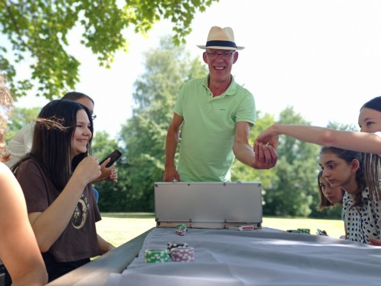 Teilnehmerinnen des Ferienprogramms spielen Poker und machen dabei Fotos