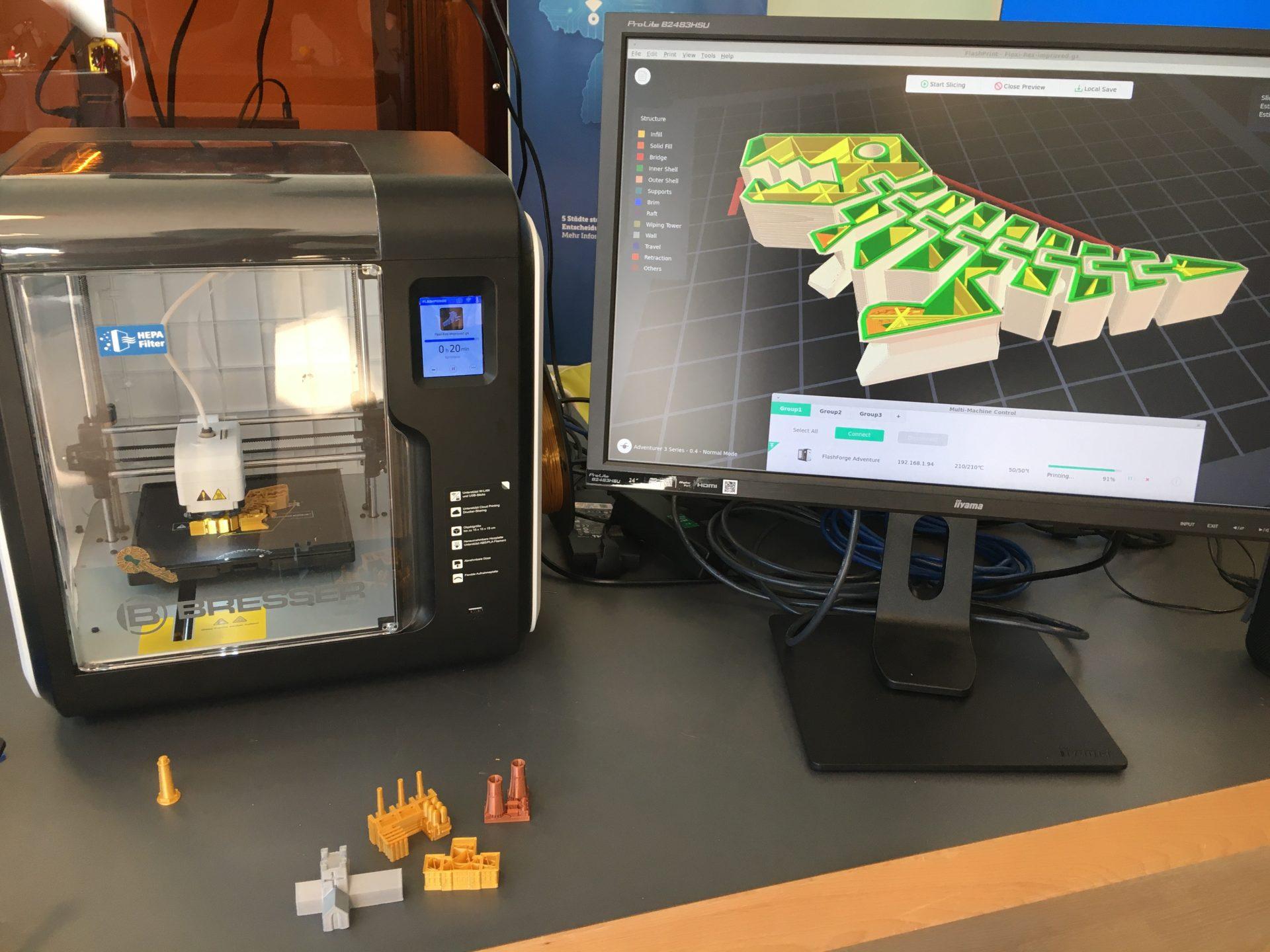 Ein kleiner 3D-Drucker neben einem Laptop, der ein designprogramm zeigt