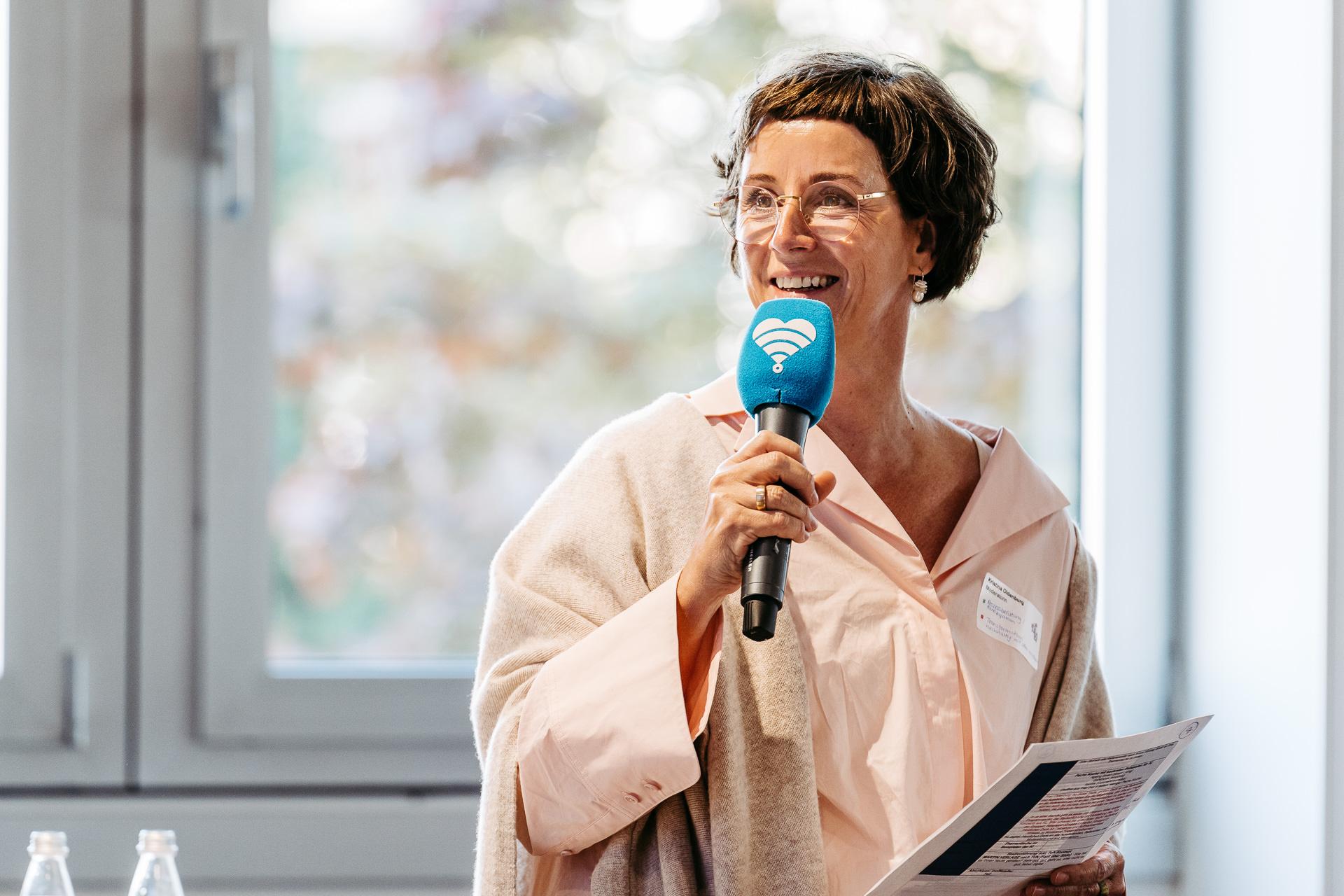 Eine Frau hält ein Mikrofon in der Hand und spricht