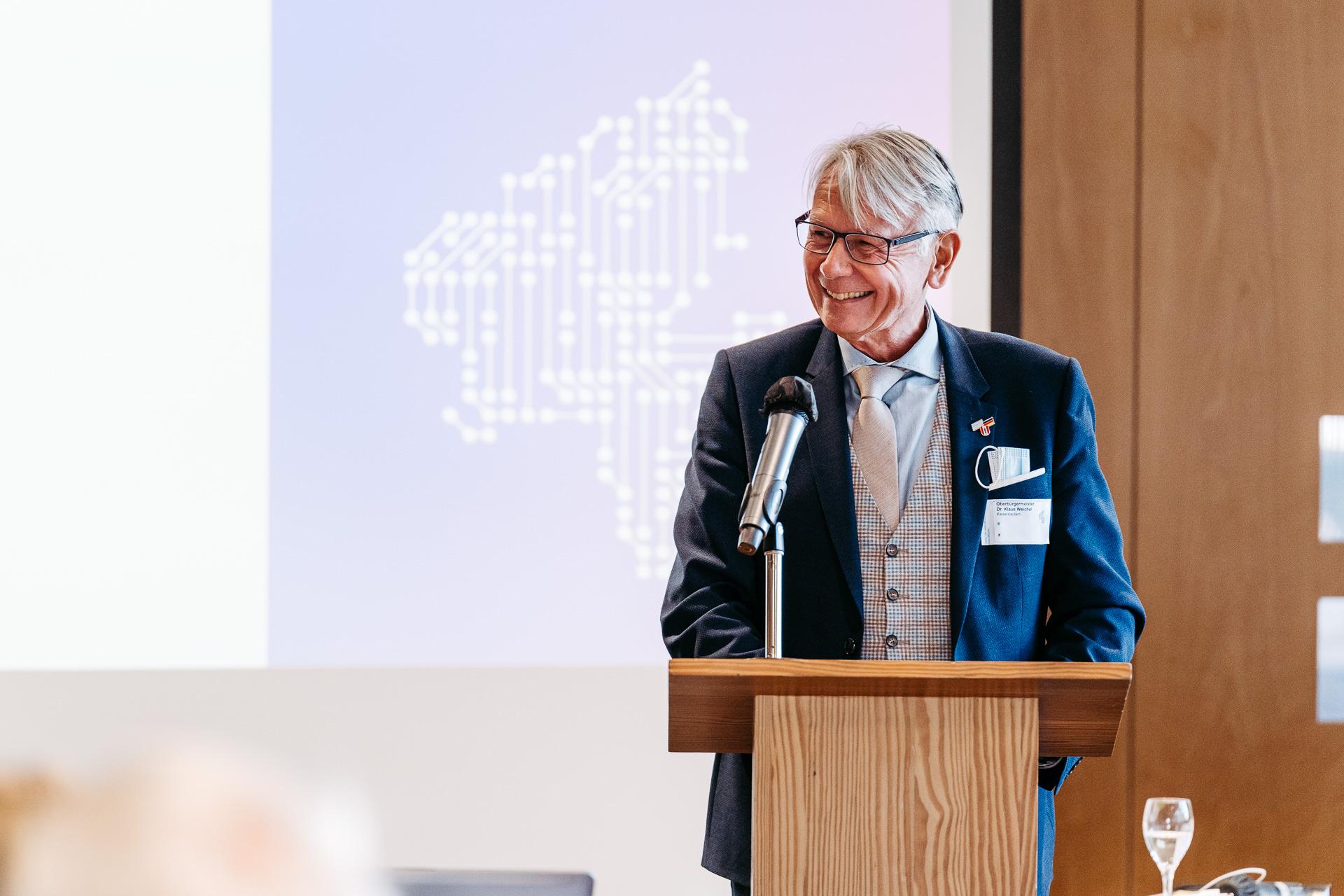 Ein Mann hält einen Vortrag und lächelt